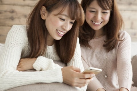 Two young women are seen together the smart phone on the sofa